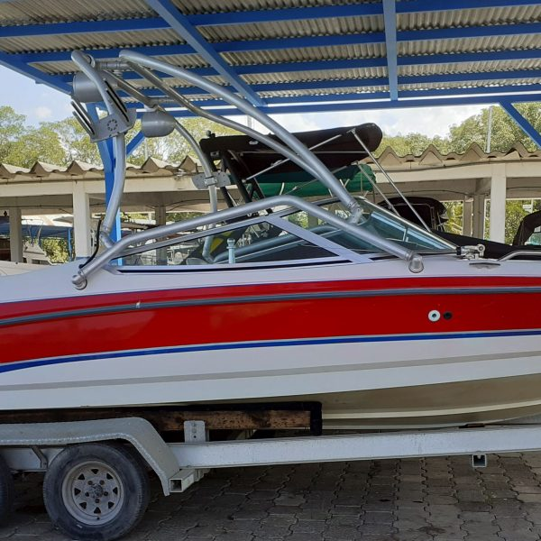 Red and white Mastercraft boat on trailer